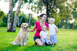 Mother and her two sons in the park with a golden retriever