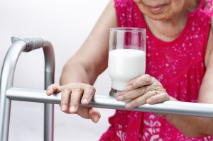 Grandmother holding a glass of milk , isolated over white backgr