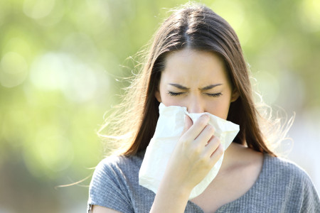 Girl sneezing and blowing in a wipe